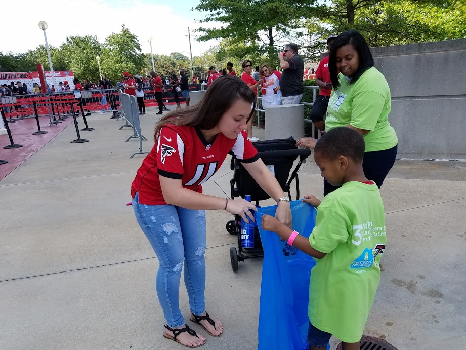 Falcons fans and Cub Scouts recycle cans