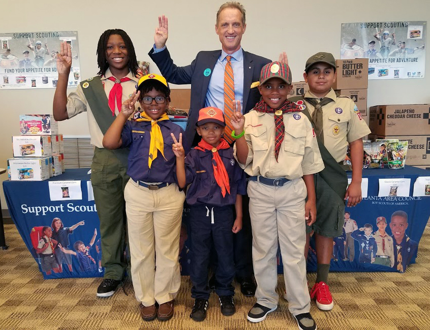 Scouts stand with Tracy Techau and their popcorn